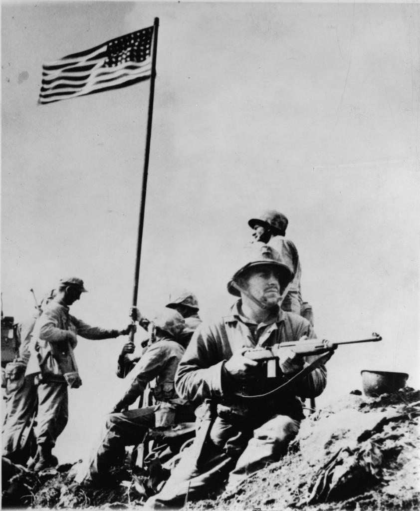 Izamiento de la bandera estadounidnse en la batalla de Iwo Jima, fotografía de Joe Rosenthal, 23 de febrero de 1945