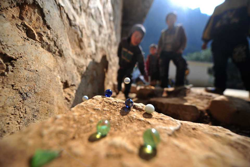 Niños, jugando canicas- Xinhua/Huang Xiaobang (archivo)