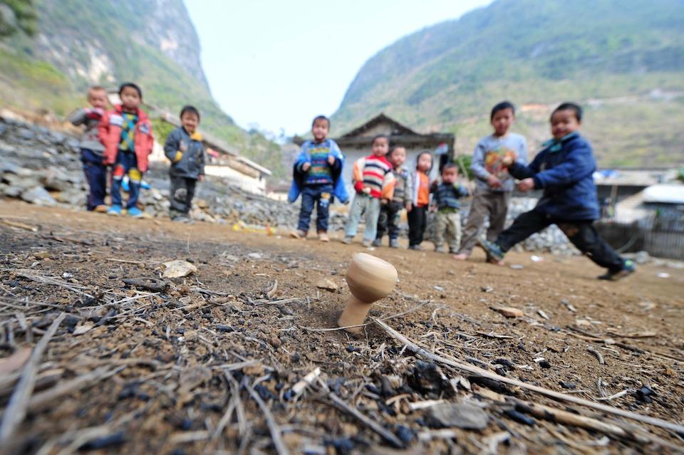 Niños jugando trompo- Xinhua:Huang Xiaobang (archivo)