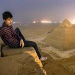 Vista noctura de la Pirámide de Giza y las luces de El Cairo al fondo, con Mister Marat en primer plano