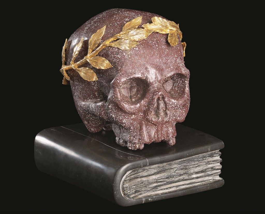Cráneo en pórfido egipcio rojo, con la corona de laurel en bronce dorado y el libro en mármol negro de Bélgica