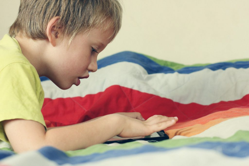 Niño autista jugando con un teléfono celular
