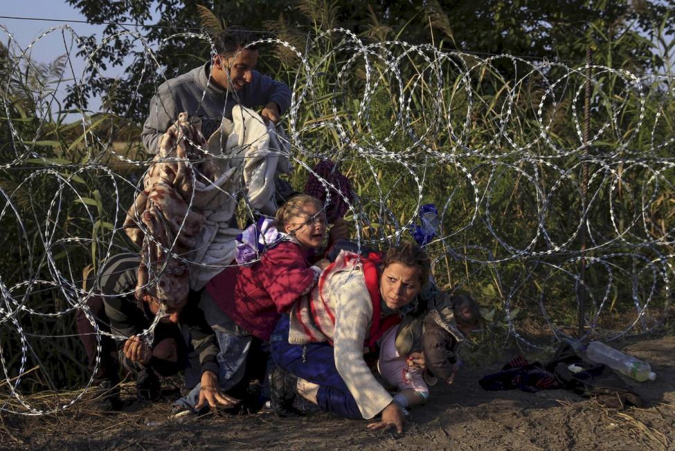 Migrantes sirios cruzan debajo de una cerca de puas al entrar en Hungria en la frontera con Serbia, cerca de Roszke, 27 de agosto de 2015- REUTERS, Bernadett Szabo