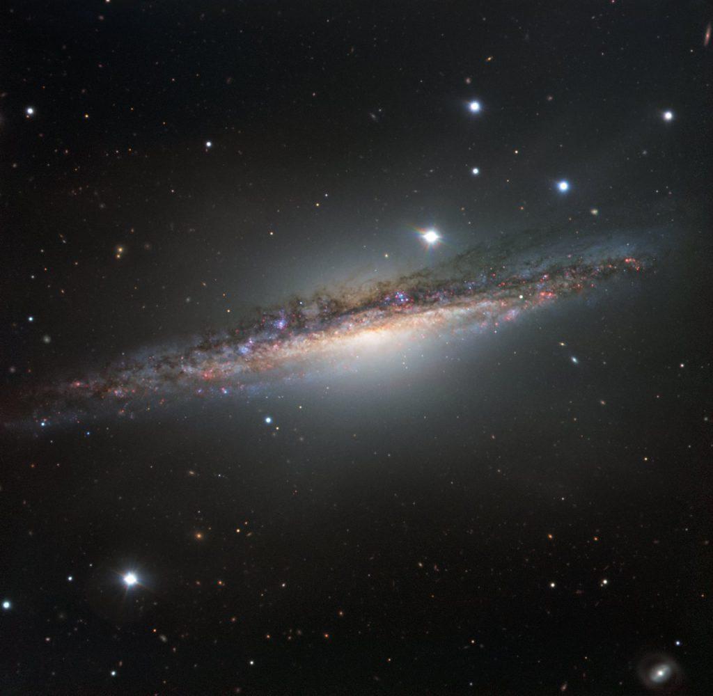 La galaxia NGC 1055, una colorida banda de estrellas, gas y polvo