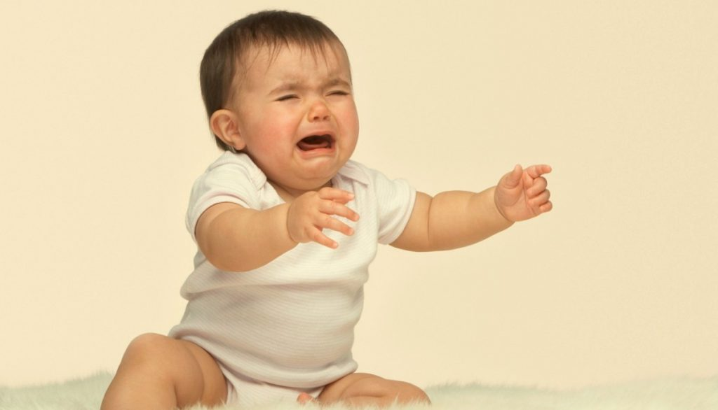 Bebé llorando con brazos extendidos