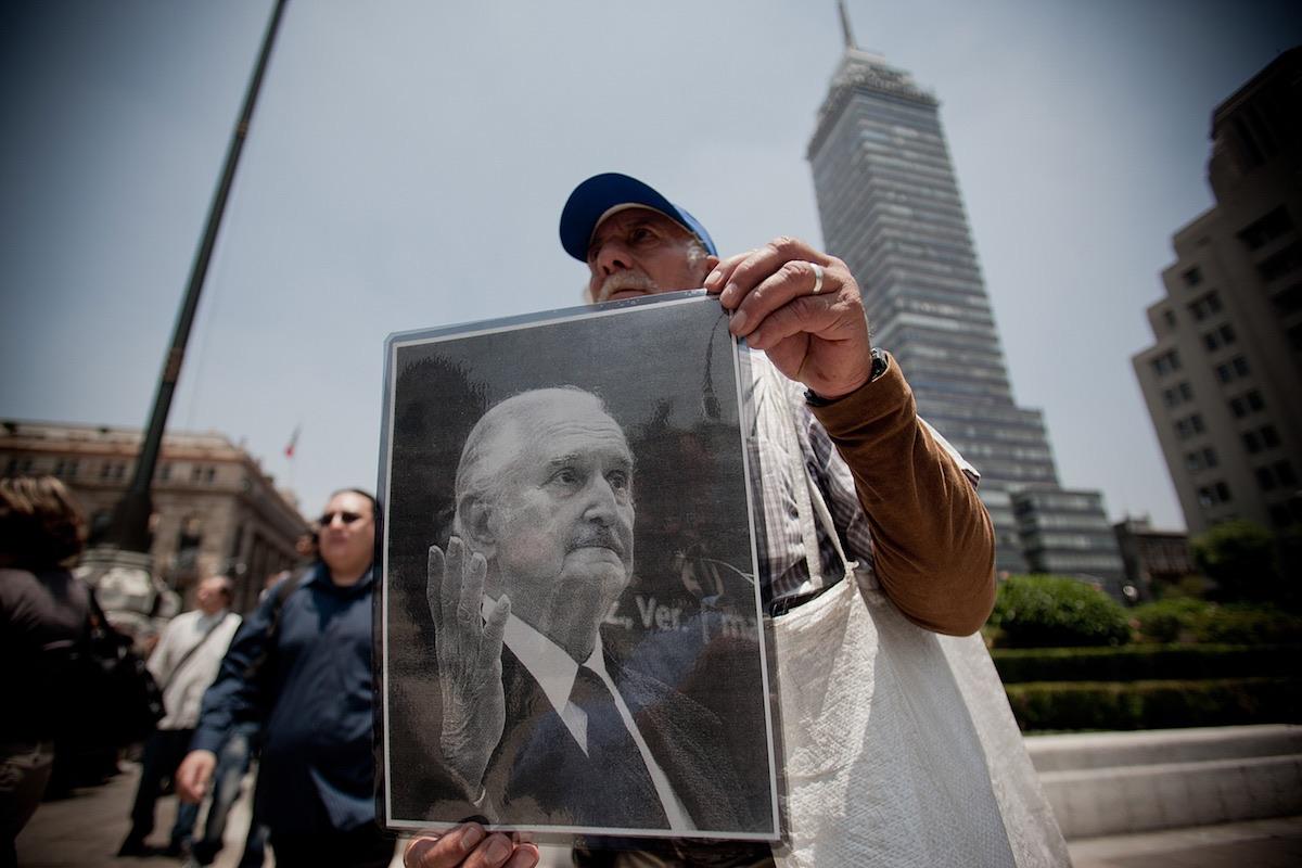 Un hombre vendía fotografías del escritor Carlos Fuentes, durante un homenaje de cuerpo presente, realizado en el Palacio de Bellas Artes, en la Ciudad de México, el 16 de mayo de 2012- Xinhua/Pedro Mera