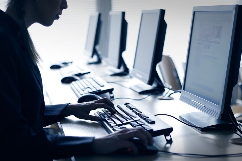 Trabajando en una computadora- AdobeStock