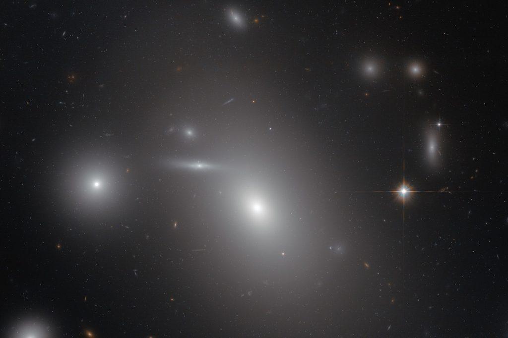 La galaxia elíptica NGC 4889, el objeto más brillante en el centro de la imagen, alberga al mayor agujero negro conocido- NASA, ESA